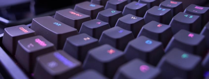 Ausschnitt einer schwarzen Tastatur mit leuchtenden Buchstaben